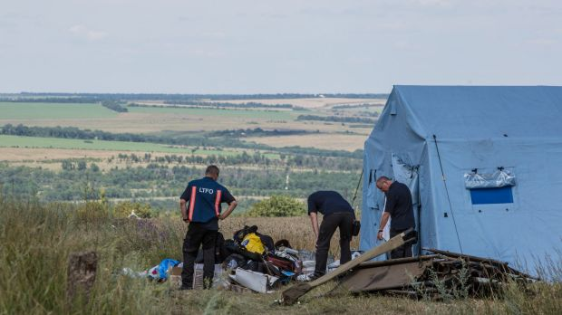 Inspectors from the Dutch government examine items at the Malaysia Airlines flight MH17 crash site.