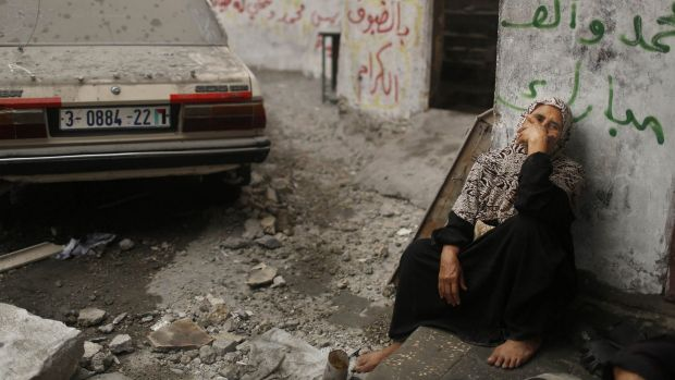 A Palestinian woman sits in a debris-strewn street in the northern Gaza Strip.