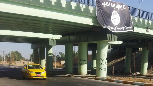 A flag of the Islamic State hangs over the entrance of the northern Iraqi city of Mosul.
