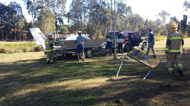 The wreckage of a light plane is removed after a crash at Runcorn, south of Brisbane.