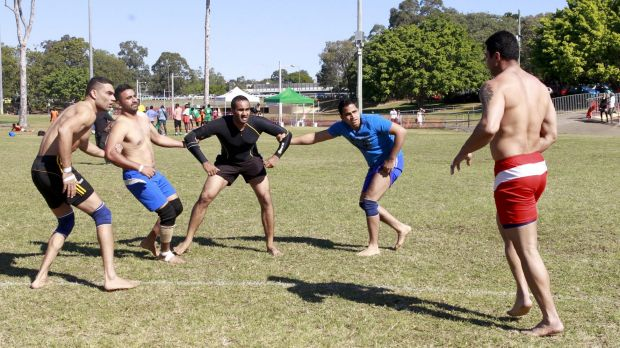 Men competing in India wrestling at World Refugee Day celebrations in Annerley.