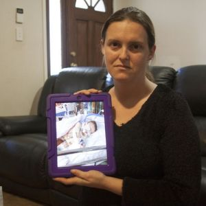 Mother Cherie holding a picture of her daughter, who can no longer receive medical marijuana.