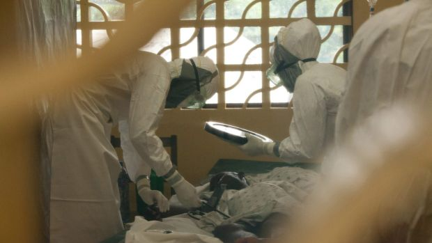 Dr Kent Brantly, left, and other health workers care for Ebola patients in Monrovia, Liberia. Dr Brantly now has the virus.