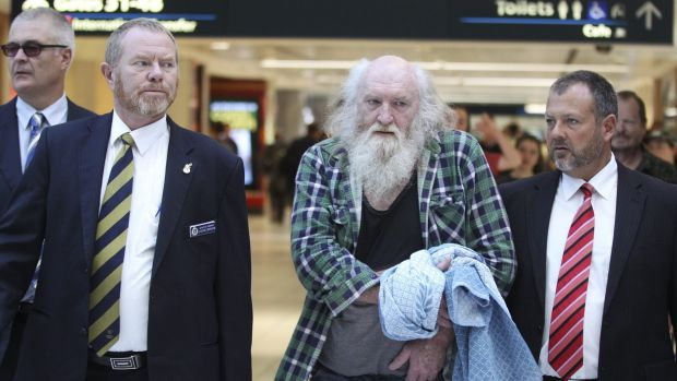 Colin Michael Newey is escorted through Sydney Airport by police after being extradited from South Australia in July.