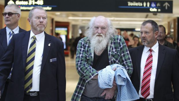 Colin Michael Newey is escorted through Sydney Airport by police after being extradited from South Australia in July 2014.