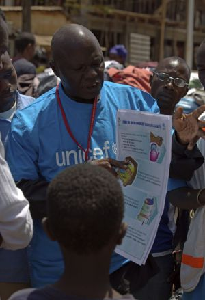 A UNICEF worker with a poster on how to prevent the spread of the Ebola.
