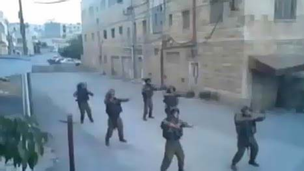 Six Israeli soldiers perform a dance routine in the deserted streets.