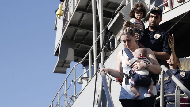 A woman evacuated from Libya carries her baby upon arrival in Piraeus, near Athens, Greece.